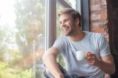 Photo smiling man looking in windows and sitting with cup of coffee on windowsill