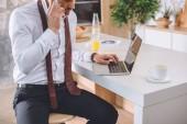 oříznutý obrázek podnikatel v bílé košili s kravatou přes krk mluví na smartphone a na notebooku pracovat v kuchyni