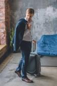 mladý podnikatel s bundou přes rameno kufrem v ložnici doma