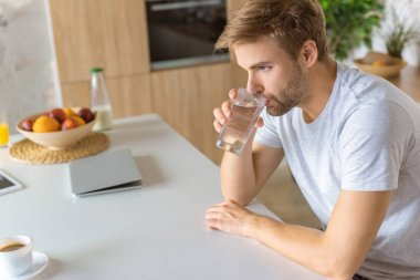 selective focus of young man drinking water at kitchen table
