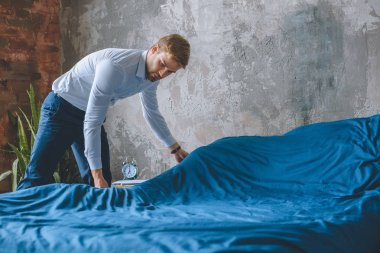 young businessman making bed in bedroom at home