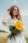 portrét usmívající se žena v bílých šatech s kytice divokých květů v poli