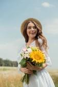 portrét veselá žena v bílých šatech s kytice divokých květů v poli