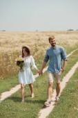 Fotografie Žena v bílých šatech s kytice divokých květů šel spolu s přítelem v poli