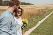 boční pohled na usmívající se žena s kytice divokých květin a přítel poblíž v poli