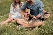 částečný pohled člověka hrál na akustickou kytaru usměvavou holku v létě podán