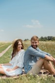 Fotografie young couple resting back to back on blanket in field with wild flowers on summer day