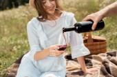 Fotografie částečný pohled člověka nalévání červeného vína do přítelkyně sklo v poli