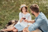 Fotografie smiling couple clinking glasses of red wine in summer field