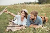 Fotografie usmívající se žena něco ukazuje přítel při odpočinku na dece dohromady v létě pole