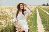 Fotografie Lächelnde Frau in weißem Kleid mit wilden Kamille Blumenstrauß sitzen auf Retro-Koffer im Feld
