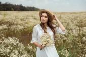 Fotografie portrét docela zamyšlená žena v bílých šatech s kyticí divoké heřmánek na louce