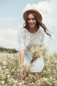 Fotografie portrét krásné ženy v bílých šatech s kyticí divoké heřmánek v poli