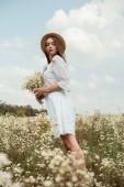 Fotografie hezká žena v bílých šatech s kyticí divoké heřmánek na louce