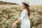 pěkně zamyšlená žena v slaměný klobouk a bílých šatech na louce s divokými květy