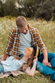 Fotografie portrait of smiling couple resting on ground in summer field