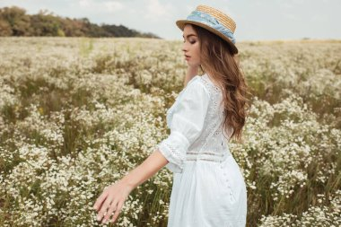 pretty pensive woman in straw hat and white dress on meadow with wild flowers