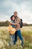 mladý pár s batohy objímání v létě pole s divokými květy