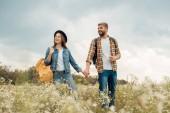 usmívající se pár s batohy, drželi se za ruce při chůzi v létě pole s divokými květy