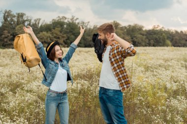 cheerful couple with backpacks in summer field with wild flowers