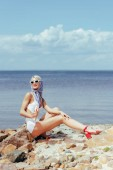 Fotografia donna elegante in costume da bagno rétro della holding del gelato e in posa sulla spiaggia rocciosa in mare