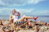 Atraktivní elegantní dívka v retro plavky odpočívá v plážovém křesle na skalnatém břehu u moře