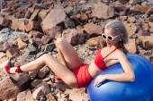 Fotografia bella ragazza bionda in bikini rosso dellannata rilassa sulla sfera blu fitness sulla spiaggia rocciosa