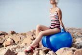 Modelka v retro pruhované plavky sedí na modré fitness míč na skalnaté pláži