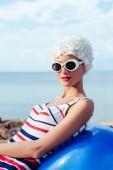 mladá žena v pruhované plavky, sluneční brýle a relaxační na fit ball bílý klobouk