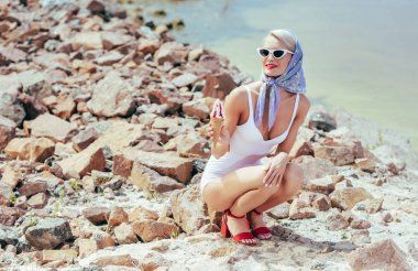 fashionable woman in vintage swimsuit holding ice cream and posing on rocky beach