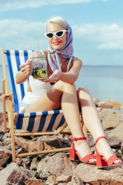 beautiful smiling girl holding lemonade in mason jar and resting in beach chair