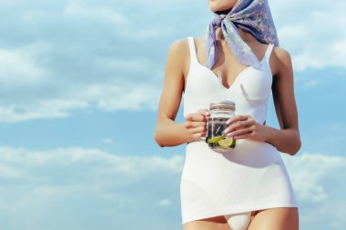 cropped view of girl in white vintage swimsuit holding mason jar with fresh lemonade