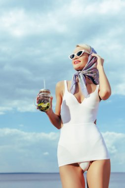 attractive girl in white vintage swimsuit holding mason jar with cocktail