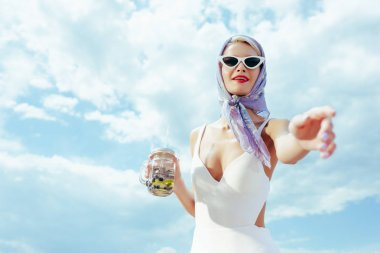beautiful fashionable woman in white vintage swimwear gesturing and holding mason jar with fresh cocktail