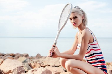 attractive blonde sportswoman in striped swimsuit holding tennis racket