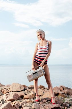 beautiful woman in swimsuit posing with vintage boombox on rocky beach