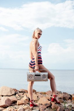 beautiful woman in retro swimsuit posing with stereo boombox on rocky beach
