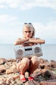 attractive woman posing with vintage boombox on rocky beach