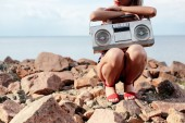 cropped view of stylish woman posing with retro boombox on rocky beach