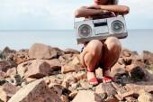 oříznutý pohled elegantní žena pózuje s retro boombox na skalnaté pláži