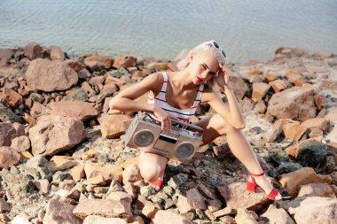 beautiful fashionable girl posing with retro boombox on rocky beach