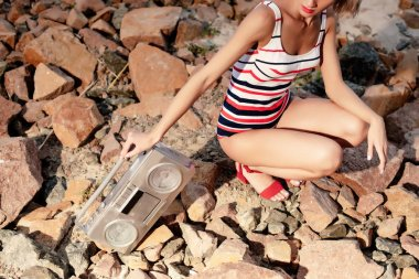 cropped view of stylish woman in striped swimsuit posing with vintage boombox on rocks