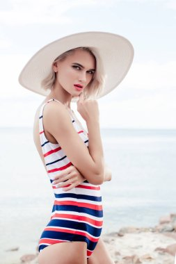 beautiful girl posing in vintage striped swimsuit and summer hat near the sea