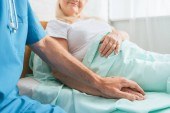 Photo cropped shot of male nurse holding hand of sick senior woman lying in hospital bed