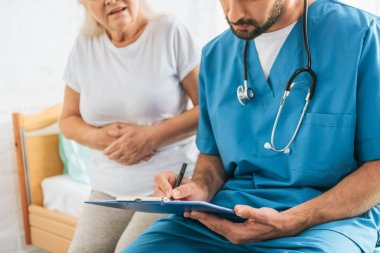 cropped shot of doctor writing on clipboard while sick senior woman sitting on hospital bed