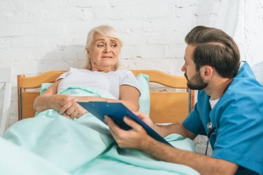 male nurse writing on clipboard and looking at sick senior woman lying in hospital bed