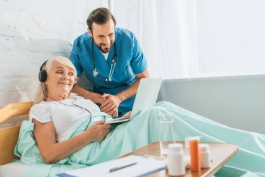 smiling young doctor looking at happy senior woman in headphones using laptop in bed