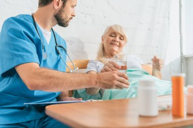 cropped shot of young doctor giving glass of water to senior woman taking medicine in bed