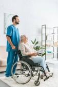 Fotografie Seitenansicht des Sozialarbeiters schieben des Rollstuhls mit senior Frau mit Zeitung und Brillen
