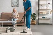Oříznout záběr sociální pracovník čištění koberců s vysavačem při starší žena čte noviny